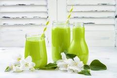 Detox, smoothie verde sano en tarros y botella Fondo rústico de madera blanco con el flor de la manzana Fotos de archivo