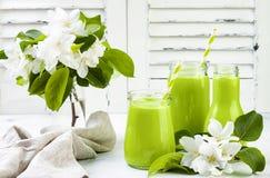 Detox, smoothie verde sano en tarros y botella Fondo rústico de madera blanco con el flor de la manzana Foto de archivo