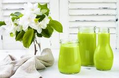 Detox, smoothie verde sano en tarros y botella Fondo rústico de madera blanco con el flor de la manzana Fotografía de archivo