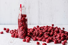 Detox water in bottle with raspberry on white wooden background.  Royalty Free Stock Images