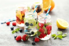 Detox water. In bottles with berries on wooden table Royalty Free Stock Photography