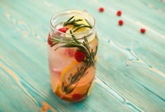 Detox water with citrus, berries and rosemary in jar. Detox water with citrus, berries and rosemary in transparent jar Royalty Free Stock Photo