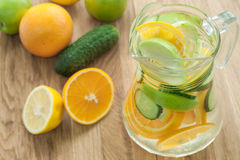Detox water with cucumber, lime, apple and orange for weightloss. Infused detox water with cucumber, lime, apple and orange in jug. Diet, detoxication Stock Images