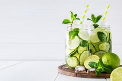 Detox water with cucumber, lime and mint and ice cubes in a glass jars. Two jars of fruit and herb infused water with cucumber, lime and mint and ice cubes on Royalty Free Stock Photography