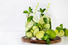 Detox water with cucumber, lime and mint and ice cubes in a glass jars. Two jars of fruit and herb infused water with cucumber, lime and mint and ice cubes on Royalty Free Stock Photo