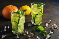 Detox water with cucumber, lime and mint on a rustic background with backlighting. Stock Image
