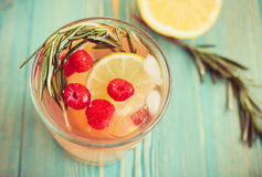 Detox water in cup with raspberry, rosemary, citrus, close-up. Detox water in cup with raspberry, rosemary and citrus, close-up, on blue wooden table, toned Stock Photos