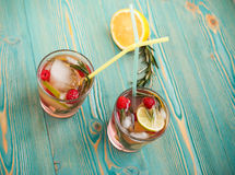 Detox water in cups with cocktail sticks. On blue wooden table Royalty Free Stock Image