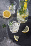 Detox water, fresh lemonade with ice, lemon and rosemary. On dark background royalty free stock images