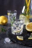 Detox water, fresh lemonade with ice, lemon and rosemary. On dark background royalty free stock image
