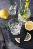 Detox water, fresh lemonade with ice, lemon and rosemary. On dark background royalty free stock photo