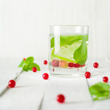 Detox water in a glass beaker. Berries and lime, red and green. Fresh mint leaves. Bright white background. Stock Images