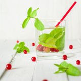 Detox water in a glass beaker. Berries and lime, red and green. Fresh mint leaves. Bright white background. Royalty Free Stock Images