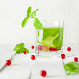 Detox water in a glass beaker. Berries and lime, red and green. Fresh mint leaves. Bright white background. Stock Image