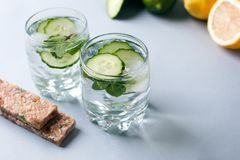 Detox water infused with sliced cucumber and springs of mint, copy space.  Royalty Free Stock Images