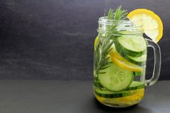 Detox water with lemon, cucumber and rosemary on slate Royalty Free Stock Image