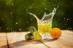 Detox water with lemon and cucumbers with splash on wooden table Stock Photo