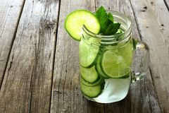Detox water with lime and cucumbers on aged wood Royalty Free Stock Photos