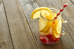 Detox water in a mason jar against wood. Nutritious detox water with lemon and raspberries in a mason jar against a wood background Royalty Free Stock Photos