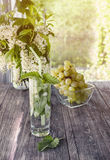 Detox water mint, grape juice and ice in a glass on a background of a bouquet of cherries and grapes on a Sunny day. The vertical Stock Photography