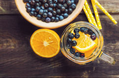 Detox water with orange and blueberries in jar stock images