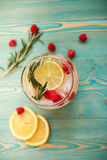 Detox water with raspberry, lime, lemon and rosemary. On turquoise colored wooden table, toned Stock Photo