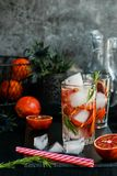 Detox water, refreshing cocktail with red blood orange, ice and rosemary. On dark background royalty free stock image