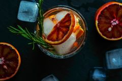 Detox water, refreshing cocktail with red blood orange, ice and rosemary. On dark background. top view. close up stock photography