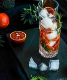 Detox water, refreshing cocktail with red blood orange, ice and rosemary. On dark background stock photos