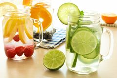 Detox water with various types of fruit in mason jars. Detox water with various types of fresh fruit and vegetables in mason jars on a table royalty free stock images