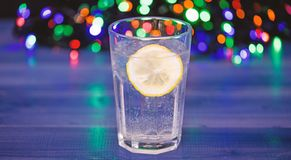 Detox after winter party. Health care concept. What to drink on christmas party. Cocktail glass with water and slice of. Lemon defocused garland lights. Detox stock images