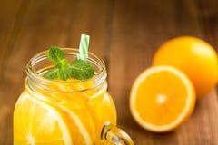 Detox woda z pomarańczowymi plasterkami w szklanym słoju z rękojeści clos Zdjęcia Stock