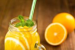 Detox woda z pomarańczowymi plasterkami w szklanym słoju z rękojeści clos Obraz Royalty Free