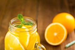 Detox woda z pomarańczowymi plasterkami w szklanym słoju z rękojeści clos Fotografia Stock