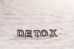 Detox word on white sand. Detox word silver and black on shiny white sand royalty free stock photos