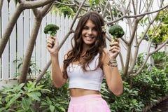 Detoxen bantar: härlig flicka som ler hållande broccoli Arkivfoton