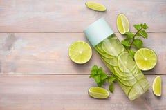 Detoxen ingav vatten med limefrukt och mintkaramellen i sportflaska, med sl arkivbild