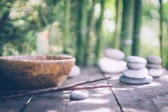 Detoxmatbegrepp: en tom träbunke, träpinnar, bambu, stenar på en gammal trätabell fotografering för bildbyråer