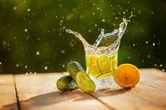 Detoxvatten med citronen och gurkor med färgstänk på trätabellen Arkivfoto