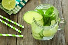 Detoxvatten med ovannämnd sikt för limefrukt och för gurkor i krus royaltyfri bild