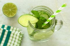 Detoxvatten med ovannämnd sikt för limefrukt och för gurkor i krus arkivfoton