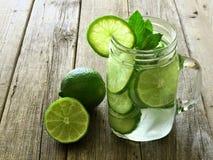 Detoxwater met kalk en komkommers op houten achtergrond Stock Fotografie