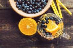 Detoxwater met sinaasappel en bosbessen in kruik stock afbeeldingen