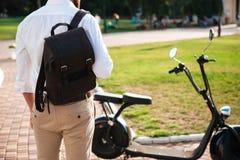 Detrás cosechada opinión el hombre con la mochila que coloca la moto cercana Fotos de archivo libres de regalías