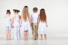 Detrás de cuatro niñas y del muchacho que colocan y que llevan a cabo las manos Imagenes de archivo