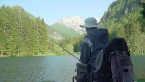 Detrás de la cámara lenta trasera del pescador perjudicado en una silla de ruedas eléctrica que pesca en el lago hermoso cerca de metrajes