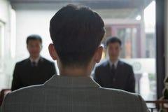 Detrás de la cabeza del hombre de negocios, dos hombre de negocios Coming Towards Him Imagen de archivo