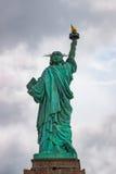 Detrás de la estatua de la libertad en día nublado fotos de archivo libres de regalías