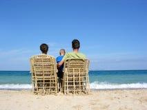 Detrás de la familia en easychairs en la playa Foto de archivo libre de regalías