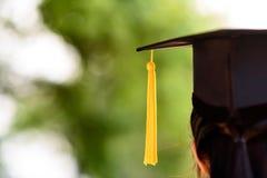 Detrás de la foto de la universidad el graduado lleva el vestido y el casquillo negro, YE Foto de archivo libre de regalías